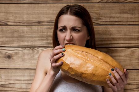 Mädchen halten das Brot in den Armen und beißt ihn ungern photo