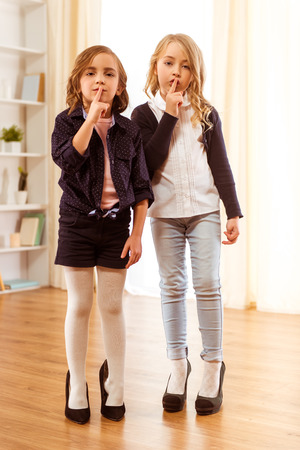 Two adorable little girl dressed in stylish clothes and shoes are too big at home on wooden floor and show be quiet tsss
