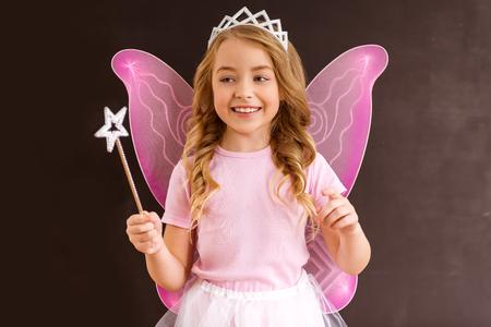 Fée de la jeune reine avec des ailes roses tenant une baguette magique sur fond sombre