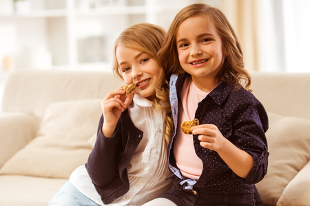 keep in: Two nice girls sitting on white sofa at home and cookies keep in the hands