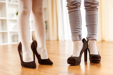 Legs of little girls on the wooden floor, shod in large adult female shoes. They are at home close-up