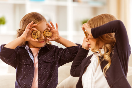 offsprings: Two beautiful girls in a dark jackets hid their eyes gingerbread at home Stock Photo