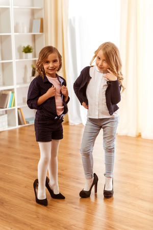 Two adorable little girl dressed in stylish clothes and shoes are too big at home on wooden floor