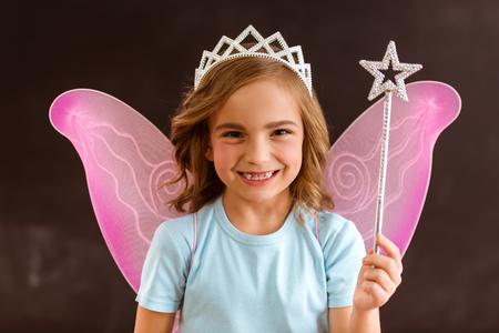 Jeune fée reine avec des ailes roses tenant une baguette magique sur un fond sombre