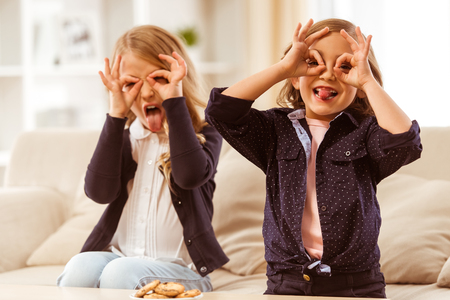 offsprings: Two nice girls in dark jackets show glasses using their  arms at home Stock Photo