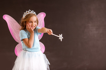 fulfilling: Young queen fairy with pink wings against a dark background waving a magic wand forward, fulfilling ones desires