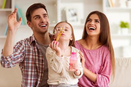 Lächelnde junge Eltern und ihr Kind sind sehr glücklich, sie sind zu Hause Standard-Bild - 51560536