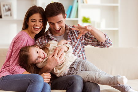 Glimlachende jonge ouders en hun kind zijn erg blij, ze zijn thuis Stockfoto