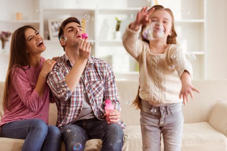 Sonreír a los padres jóvenes y su hijo son muy felices, están en casa