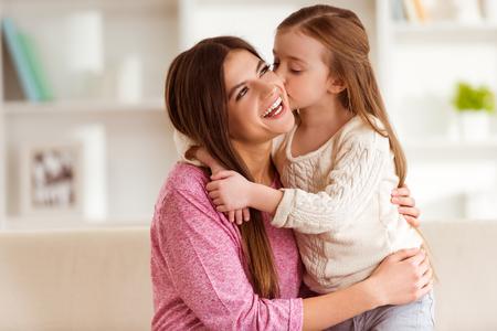 Daughter küssen ihre Mutter glücklich und umarmt sie, sie sind zu Hause photo