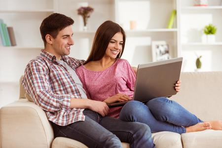 Schöne junge Leute auf der Couch zu Hause, voller Gefühle für einander sitzen photo