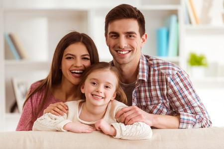 Lächelnde junge Eltern und ihr Kind sind sehr glücklich, sie sind zu Hause photo