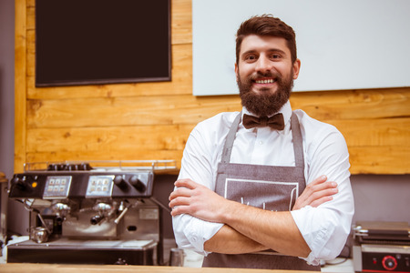 cross armed: Young handsome barista with beard in shirt and bow tie smiling while standing at the bar counter Stock Photo
