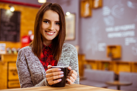 hapiness: Beautiful young woman in casual clothes drinking coffee and smiling while sitting in a cafe Stock Photo