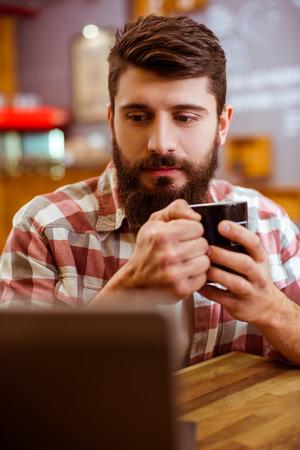 Junger moderner Geschäftsmann mit Bart in Freizeitkleidung mit Laptop und Kaffee trinken, während sitzen in einem Café photo