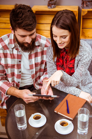 Top Blick auf schöne junge Paar in Freizeitkleidung mit Tablet und Kommunikation während sitzen in einem Café photo
