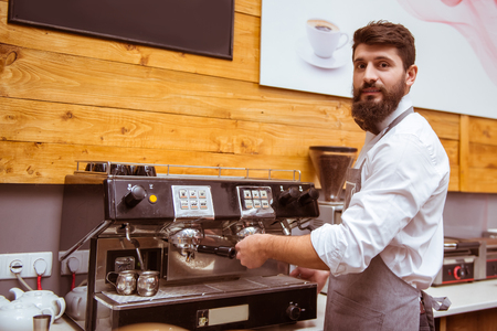 Junge gut aussehend Barista mit Bart in Hemd und Krawatte Kaffee kochen Bogen photo