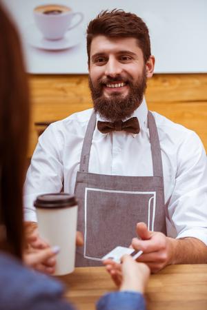 Junge gut aussehend Barista mit Bart in Hemd und Fliege eine Tasse geben und eine Kreditkarte nehmen, während an der Theke stehen photo