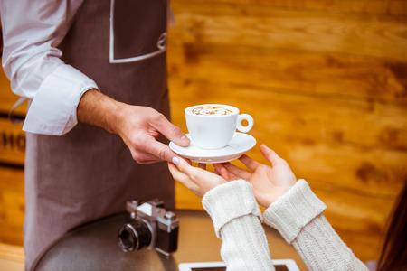 Junge schöner Kellner mit Bart eine Tasse schöne junge Frau in einem Cafe geben, close-up photo