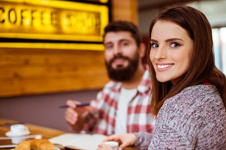 Schöne junge Paar in Freizeitkleidung zu arbeiten und zu kommunizieren, während sitzen in einem Café photo