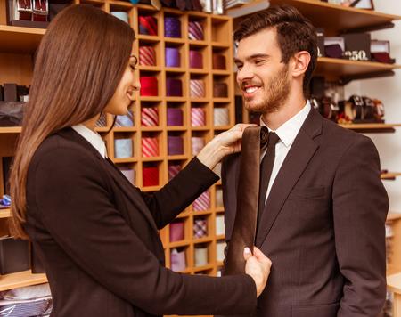 3c56bba63b8 #51688380 - 아름 다운 젊은 여성 점원 웃 고 양복 가게에 현대 잘 생긴 젊은 사업가에 넥타이를 제공