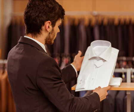 customer tailor: Modern young handsome businessman looking and choosing classical shirt in the suit shop Stock Photo