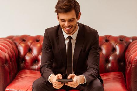 in  shirt: apuesto hombre de negocios joven moderna vestida en traje cl�sico utilizando un tel�fono mientras se est� sentado en un sof� en la tienda del juego Foto de archivo