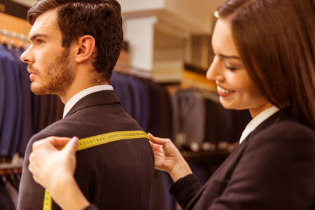Young beautiful female shop assistant taking measurements of a modern young handsome businessman in the suit shop Stock Photo