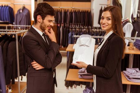 Giovane bello assistente femminile negozio di consultazione di un moderno uomo d'affari bello del negozio vestito Archivio Fotografico