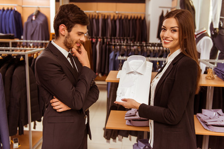 Young beautiful female shop assistant consulting a modern young handsome businessman in the suit shop
