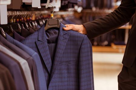 in  shirt: Una mano de un moderno hombre de negocios hermoso joven que elige el juego cl�sico de la fila de trajes en la tienda del juego, primer plano Foto de archivo