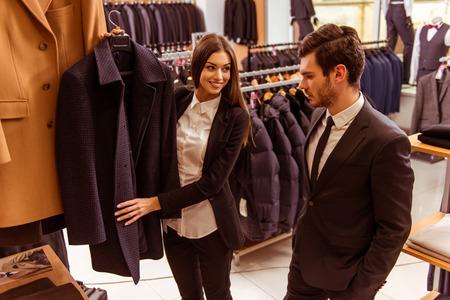 1ce595c322d #51687969 - 아름 다운 젊은 여성 점원 웃 고 소송 상점에서 현대 잘 생긴 젊은 사업가에 양복을 제공
