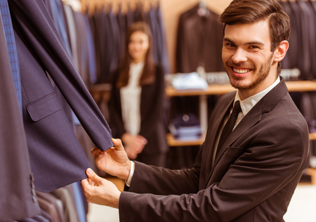 c0d43252557 #51687970 - 백그라운드에서 서있는 젊은 아름 다운 여성 상점 조교하는 동안 클래식 양복을 선택 하 고 양복가 게에서 선택하는 현대  젊은 잘 생긴 사업가