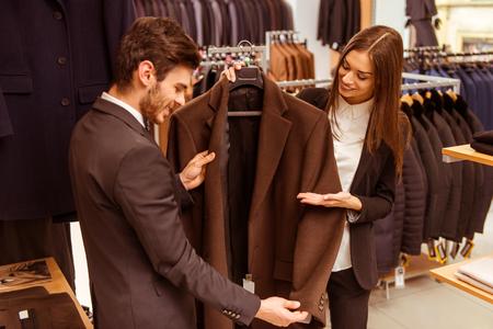 286ee9b9247 #51687976 - 아름 다운 젊은 여성 점원 웃 고 소송 상점에서 현대 잘 생긴 젊은 사업가에 양복을 제공