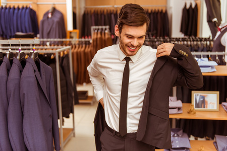 chaqueta: joven apuesto hombre de negocios moderna sonriendo y tratando de traje clásica en la tienda de traje Foto de archivo