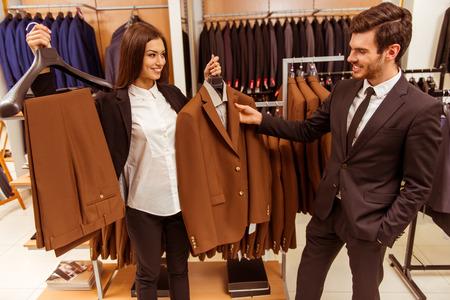 136e4823767 #51688152 - 아름 다운 젊은 여성 점원 웃 고 소송 상점에서 현대 잘 생긴 젊은 사업가에 양복을 제공