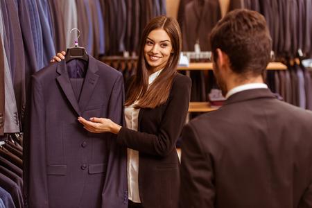 636ddba22f1 #51688151 - 미소하고 양복점에서 현대 젊은 잘 생긴 사업가 양복을 제공 하 고 젊은 아름 다운 여성 상점 조교