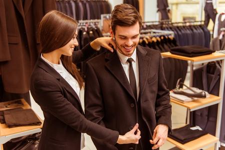 若い美しい女性店員笑顔とスーツ ショップでジャケットを試着するモダンな若いハンサムな実業家を支援