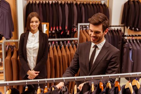 in  shirt: Moderno joven apuesto hombre de negocios sonriente y la elecci�n de traje cl�sica en la tienda del juego, mientras que una joven y bella ayudante de tienda femenino que se coloca en el fondo