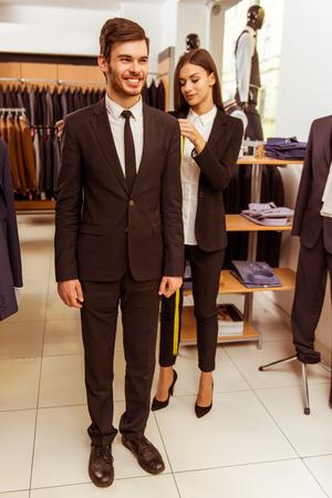 Junge schöne weibliche Verkäuferin Messungen eines modernen jungen schönen Geschäftsmann im Anzug Geschäft nehmen photo