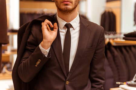Modern young handsome businessman dressed classical suit holding a overcoat while standing in the suit shop, close-up