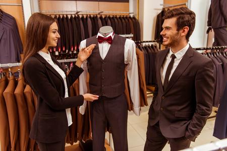 mannequin: Jeune assistant belle boutique femme souriante et offrant un costume sur un mannequin à un beau jeune homme d'affaires moderne dans le magasin de costume