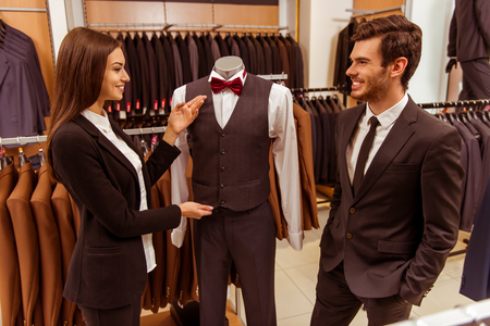Young beautiful female shop assistant smiling and offering a suit on a mannequin to a modern young handsome businessman in the suit shop