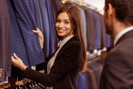 e84f6462fef #51687733 - 미소하고 양복점에서 현대 젊은 잘 생긴 사업가 양복을 제공 하 고 젊은 아름 다운 여성 상점 조교