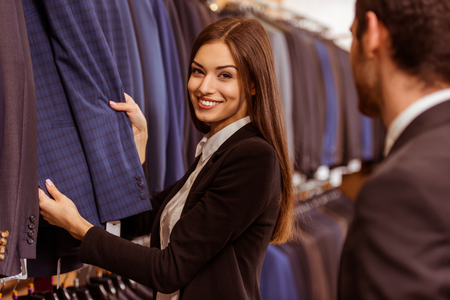 Junge schöne Frau Verkäuferin lächelnd und mit einem Anzug auf eine moderne junge hübsche Geschäftsmann im Anzug shop bietet photo