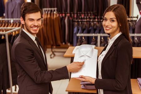 Junge schöne weibliche Verkäuferin eine moderne junge hübsche Geschäftsmann im Anzug Shop Beratung photo
