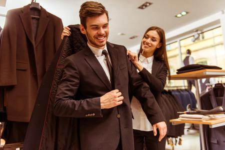 Junge schöne weibliche Verkäuferin lächelnd und mit einem modernen schöne junge Unternehmer zu helfen auf eine Jacke in der Anzug-Shop zu versuchen, photo