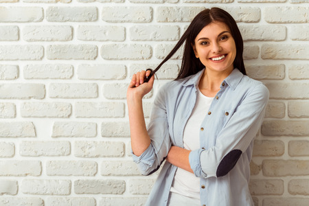 brick: Portrait of beautiful girl in casual clothes playing with her hair, looking in camera and smiling while standing against white brick wall