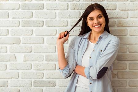 ladrillo: Retrato de la muchacha hermosa en ropa casual de jugar con su pelo, mirando en la c�mara y sonriendo mientras est� de pie contra la pared de ladrillo blanco