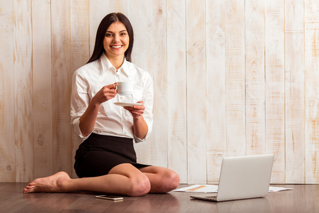 Beautiful girl in white shirt holding a cup, looking in camera and smiling while sitting near laptop against wooden background